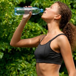 stock photo of a woman drinking water after running